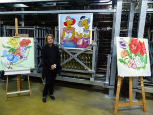 Dany Rodriguez in front of her paintings. She has displayed her paintings throughout France.