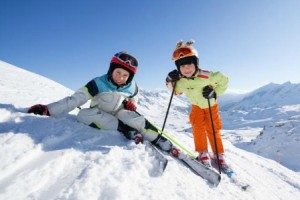 happy children in skiing outfit in snowy mountains